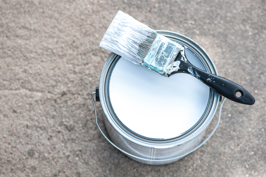 Close-up view of aluminium paint can on concrete with white paint and dirty paint brush, shallow DOF