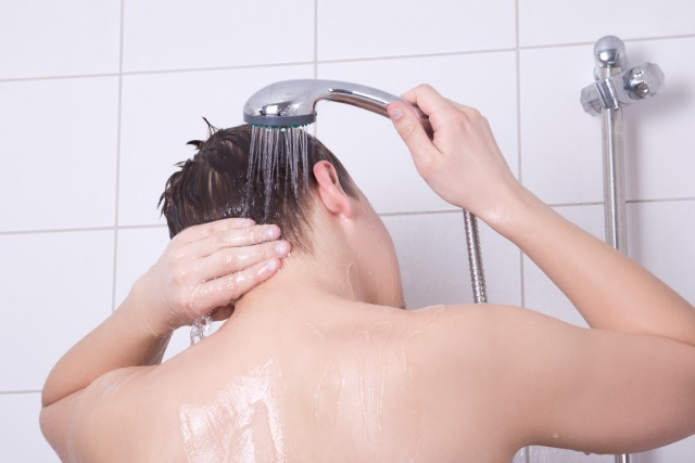 A picture of a man washing his hair with a shower head.