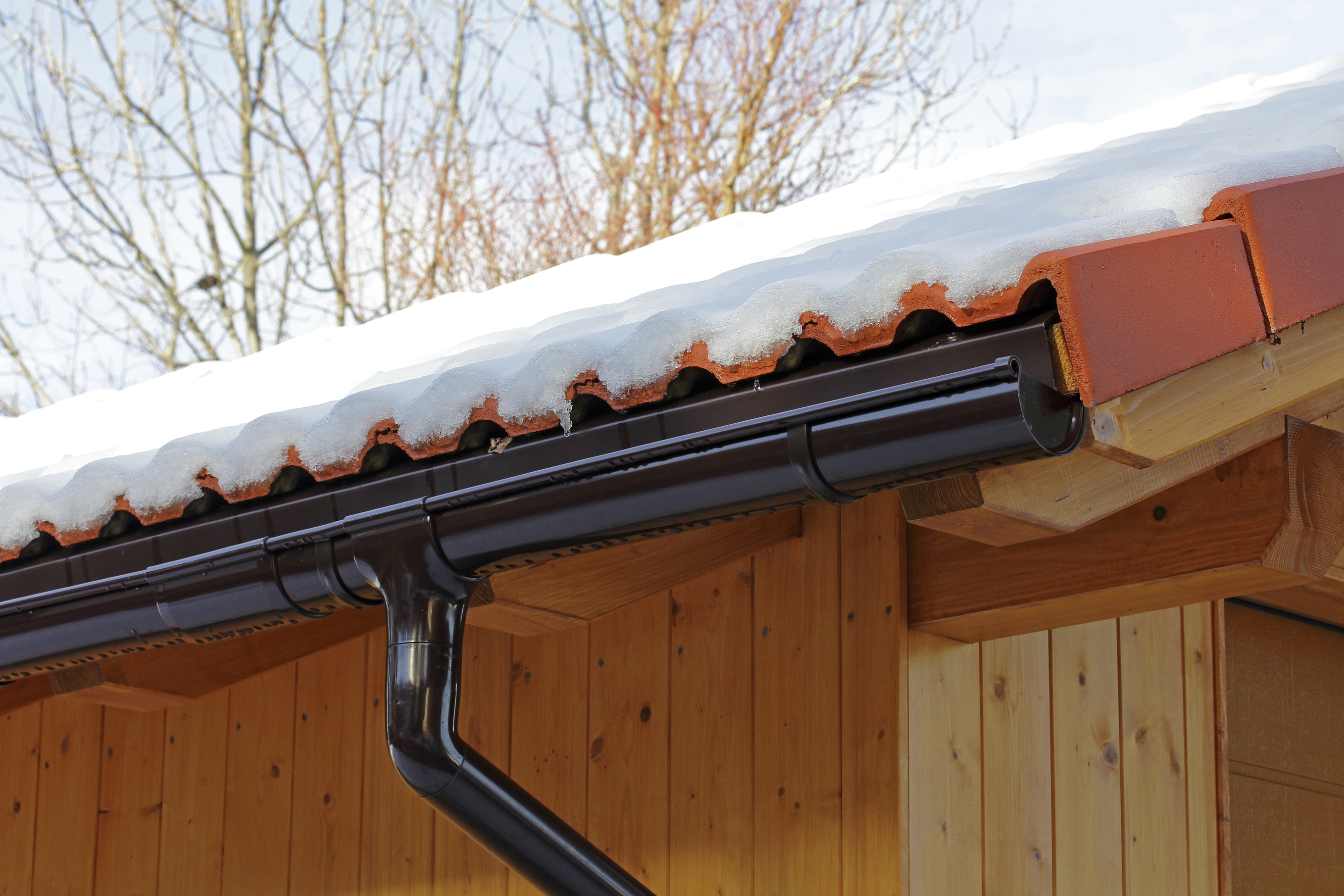 wooden roof with rain gutter and drainpipe in winter